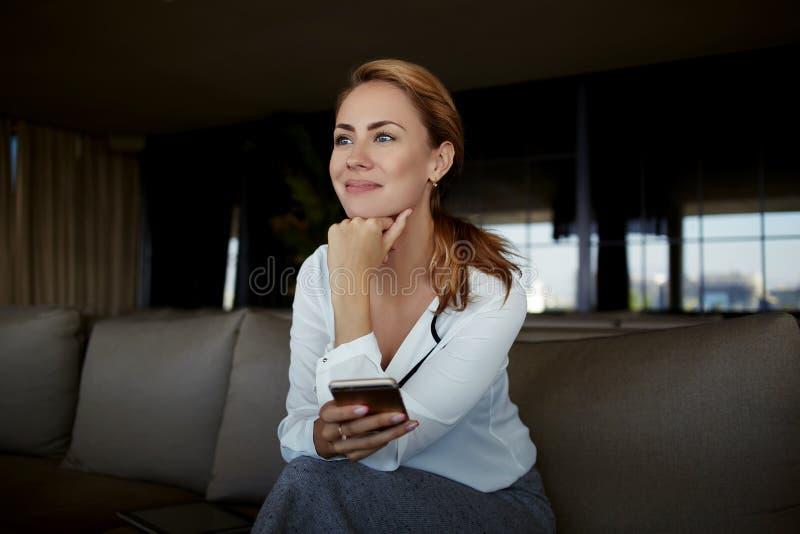 Durchdachte Frau mit dem Handy in der Hand, der während des Arbeitsbruches beim Sitzen auf Sofa im modernen Caféinnenraum stillst stockfoto