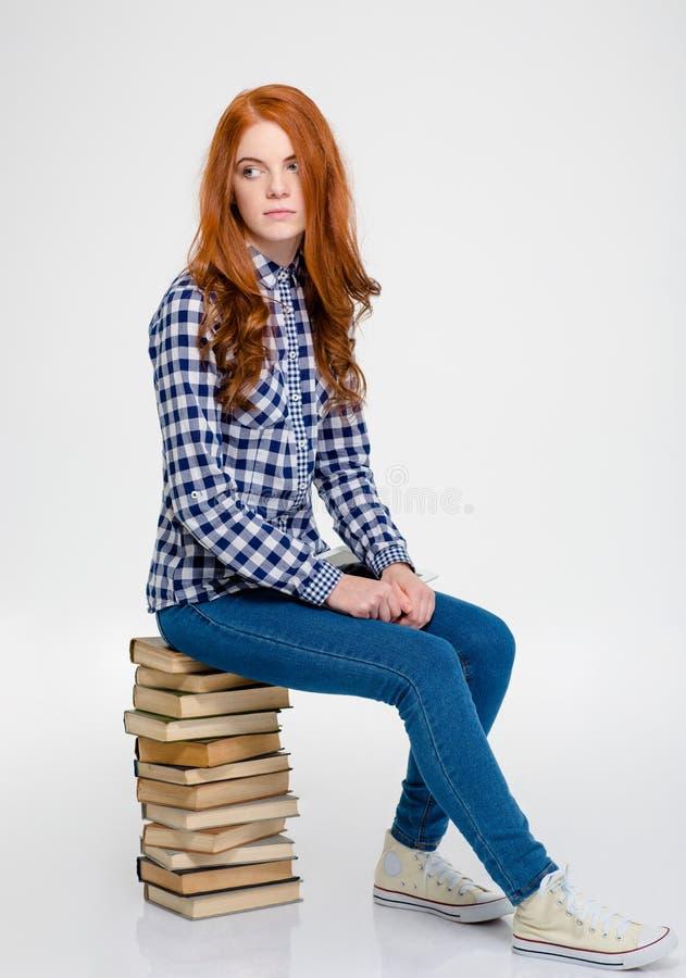 Durchdachte Frau mit dem roten Haar, das auf Büchern und dem Denken sitzt lizenzfreie stockfotos