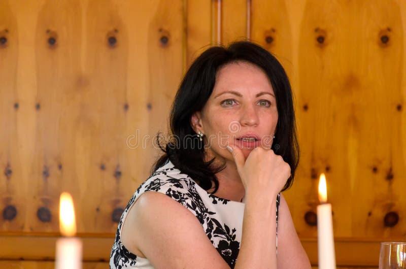 Durchdachte Frau mit ihrer Hand zu ihrem Kinn stockfoto