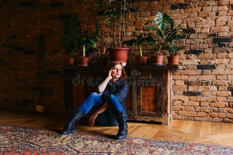 Durchdachte Frau von mittlerem Alter, die auf dem Boden sitzt lizenzfreie stockfotos
