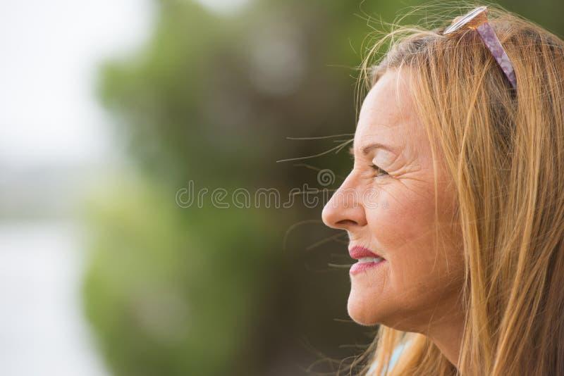 Durchdachte freundliche ältere Frau im Freien stockbild