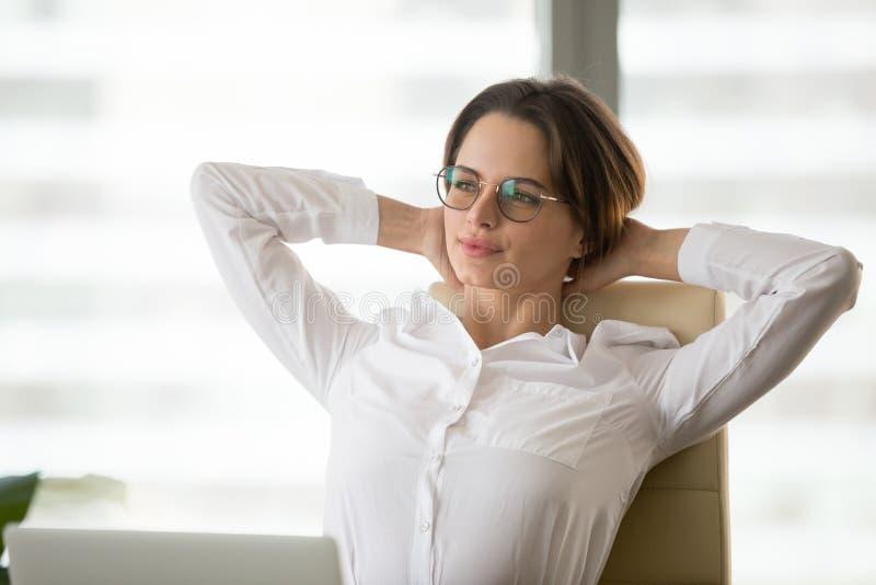 Durchdachte Geschäftsfrau, die im Stuhl nach der Arbeit sich entspannt sich lehnt lizenzfreie stockfotos