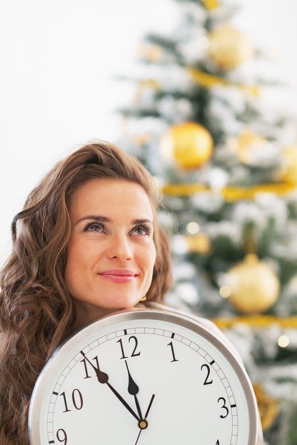 Durchdachte junge Frau, die Uhr vor Weihnachtsbaum zeigt stockbilder