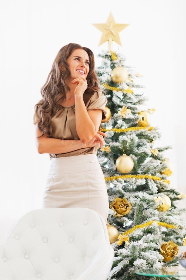 Durchdachte junge Frau, die vor Weihnachtsbaum steht stockfotografie