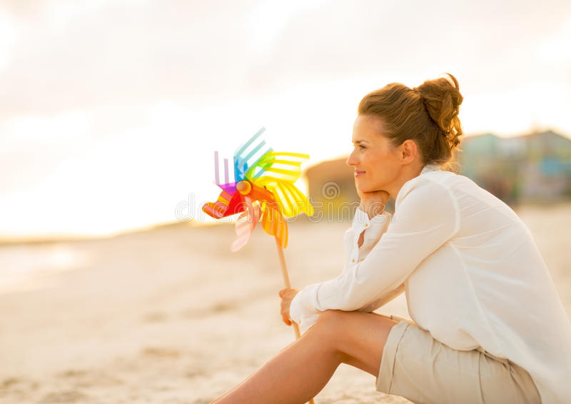 Durchdachte junge Frau mit buntem Windmühlenspielzeug lizenzfreies stockfoto