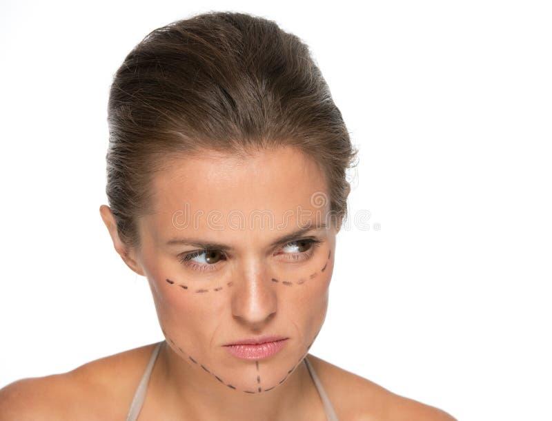 Durchdachte junge Frau mit Kennzeichen der plastischen Chirurgie lizenzfreie stockbilder