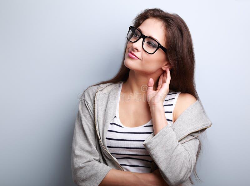 Durchdachte junge zufällige Frau, die auf leerem Kopienraum schaut stockfotografie
