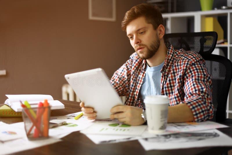 Durchdachte männliche Person, die zum digitalen Tablettenschirm beim Sitzen im modernen Innenraum dem Tisch, erfahren betrachtet lizenzfreie stockbilder