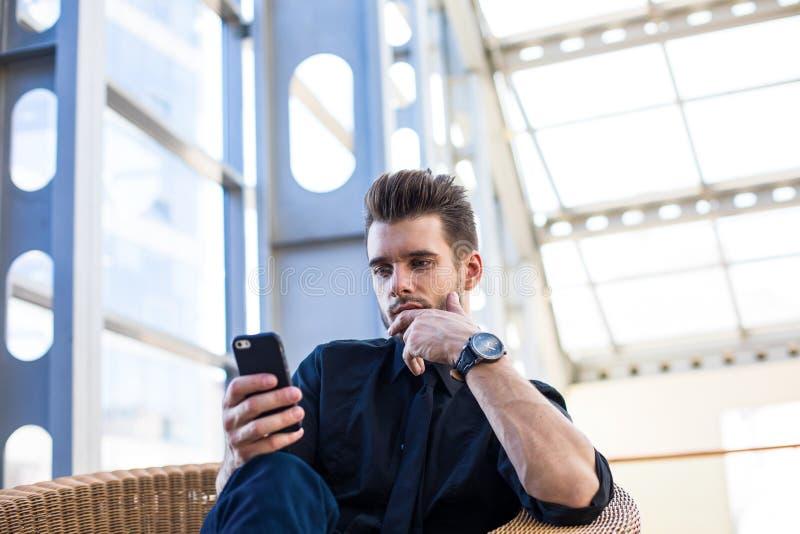 Durchdachte Mannführung, die Apps am Handy, sitzend in Unternehmen während des Arbeitstages installiert lizenzfreies stockbild