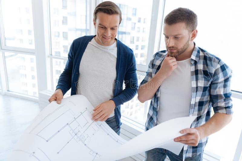 Durchdachte nette Männer, welche die technische Konstruktionszeichnung betrachten stockbilder