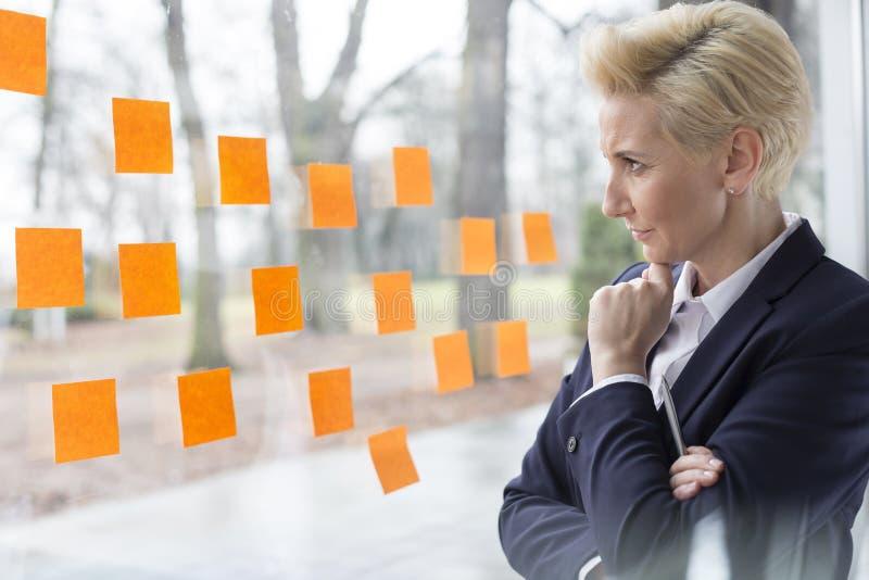 Durchdachte reife Geschäftsfrau, die orange klebende Anmerkungen über Glasfenster im Büro betrachtet stockfoto