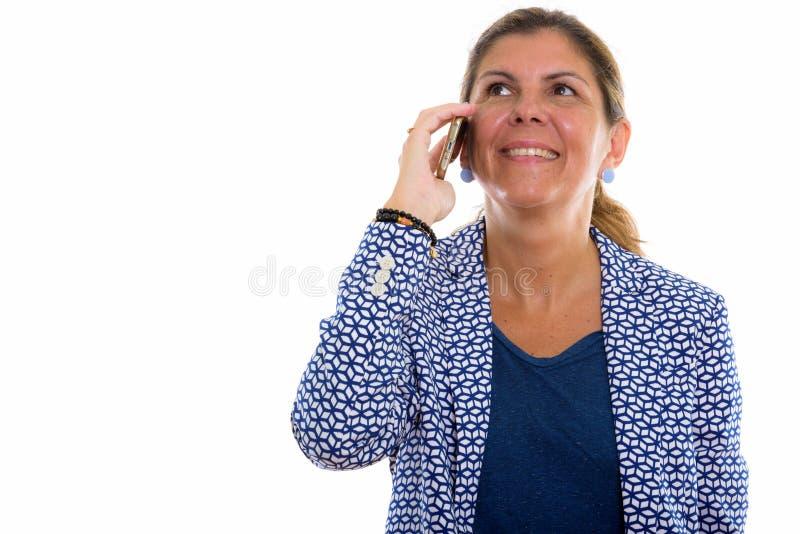 Durchdachte reife glückliche lächelnde Geschäftsfrau bei der Unterhaltung auf m lizenzfreies stockfoto