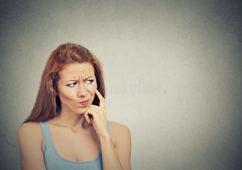 Durchdachte skeptische misstrauische junge Frau stockfotos