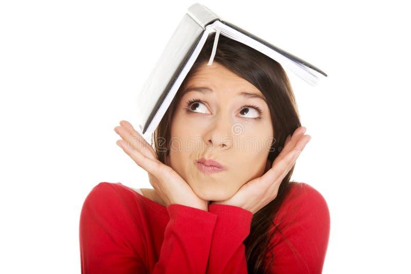 Durchdachte Studentenfrau mit ihrer Anmerkung über Kopf stockfoto