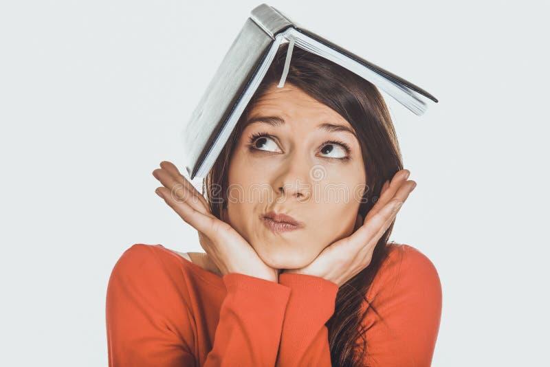Durchdachte Studentenfrau mit ihrer Anmerkung über Kopf stockbild