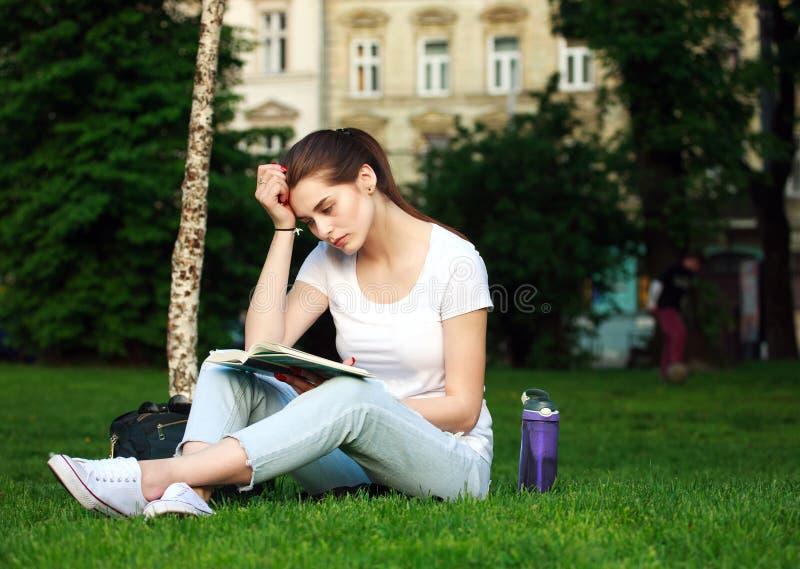 Durchdachte Studentin in einem Stadtpark ein Buch lesend lizenzfreies stockfoto