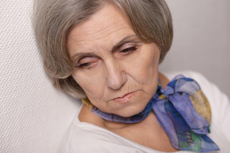 Durchdachte traurige ältere Frau stockfotografie