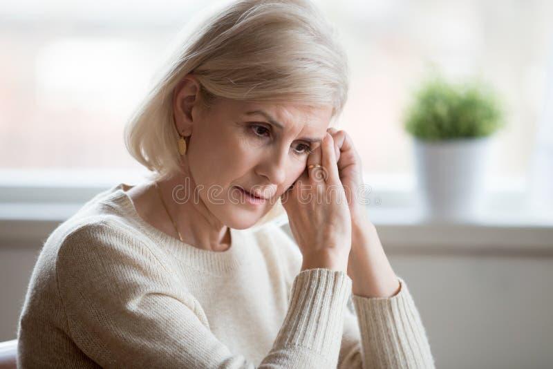 Durchdachte traurige mittlere Greisin, die dem blauen Denken an anxiet glaubt stockfotografie
