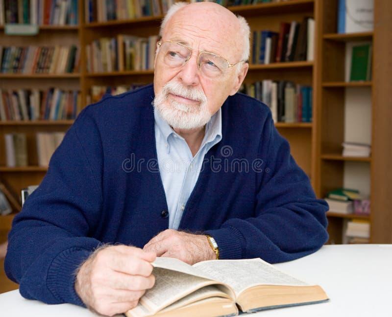 Durchdachter Älterer in der Bibliothek lizenzfreie stockbilder