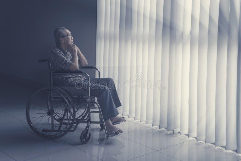Durchdachter älterer Mann, der auf Rollstuhl sitzt lizenzfreies stockbild