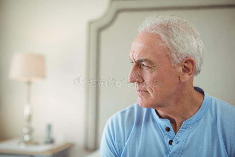 Durchdachter älterer Mann, der im Bettraum sitzt stockbild