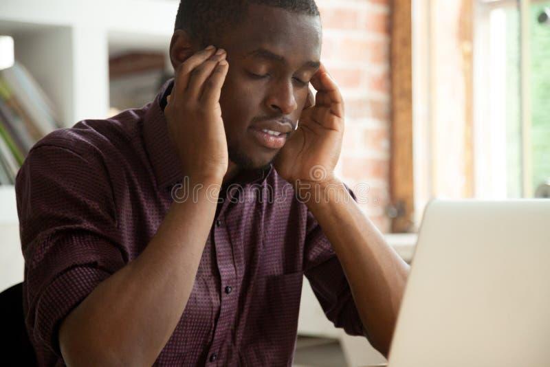 Durchdachter Afroamerikaner, der das Problem arbeitet am Laptop löst lizenzfreie stockfotografie