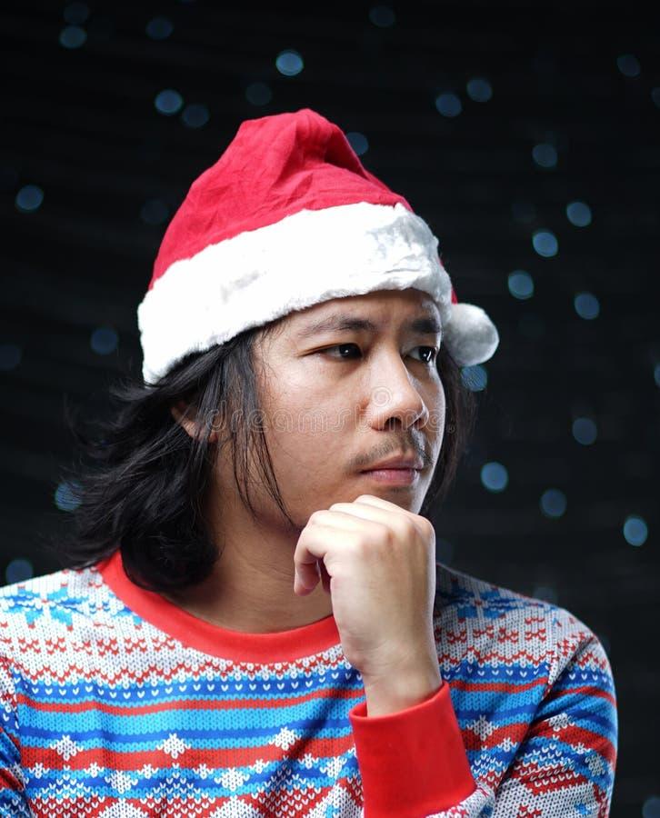 Durchdachter asiatischer Mann, der Santa Hat und Weihnachtsstrickjacke trägt stockfotografie