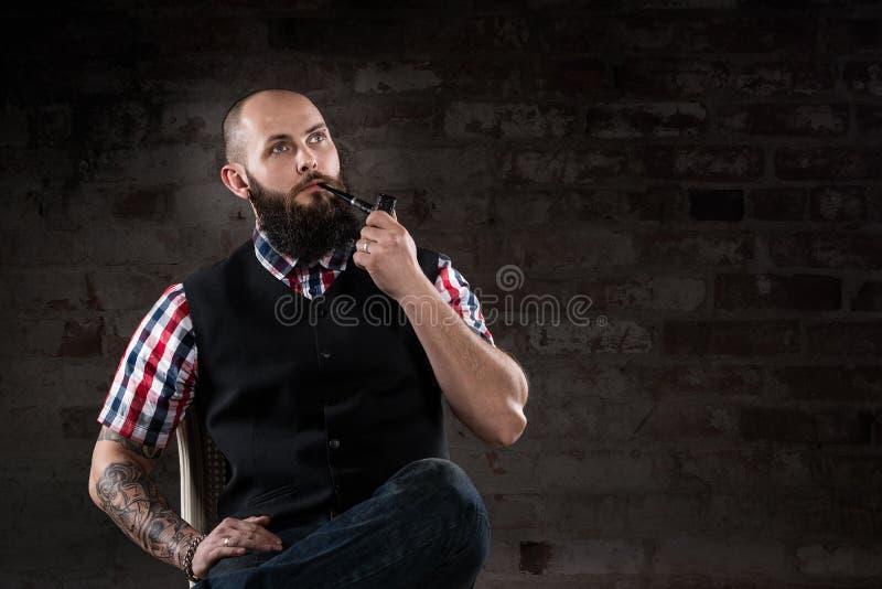 Durchdachter bärtiger Mann in einem karierten Hemd stockfotos