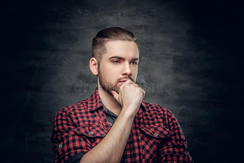Durchdachter bärtiger Mann kleidete in einem roten Vlieshemd an stockfoto