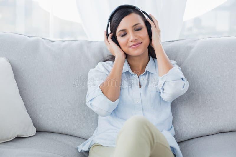 Durchdachter Brunette, der Musik hört lizenzfreie stockfotografie