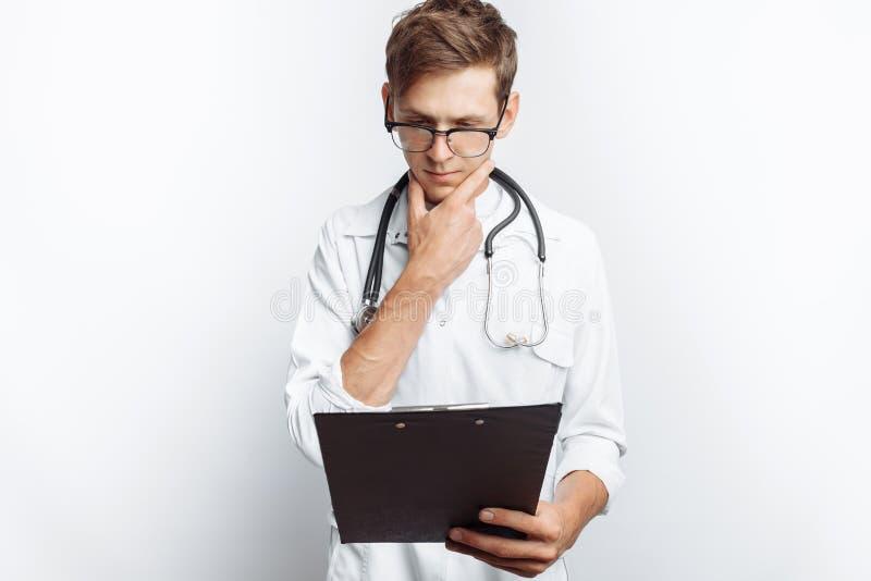 Durchdachter Doktor, die Dokumente betrachtend und macht Anmerkungen in den Dokumenten, ein junger Student mit einem Ordner in se lizenzfreie stockfotografie