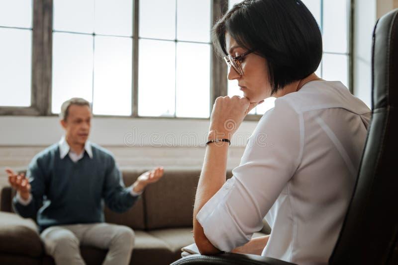 Durchdachter dunkelhaariger weiblicher Psychotherapeut, der aufmerksam auf ihren Kunden hört stockfotografie