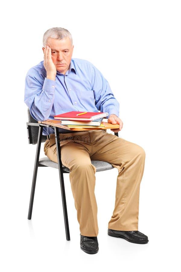 Durchdachter fälliger Mann, der auf einem Klassenzimmerstuhl sitzt lizenzfreie stockbilder