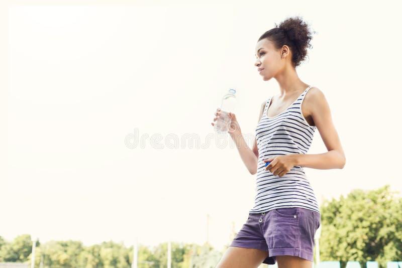 Durchdachter Frauenläufer hat Bruch, Trinkwasser lizenzfreie stockfotografie