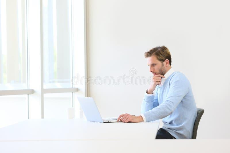 Durchdachter Geschäftsmann auf Laptop lizenzfreie stockfotos