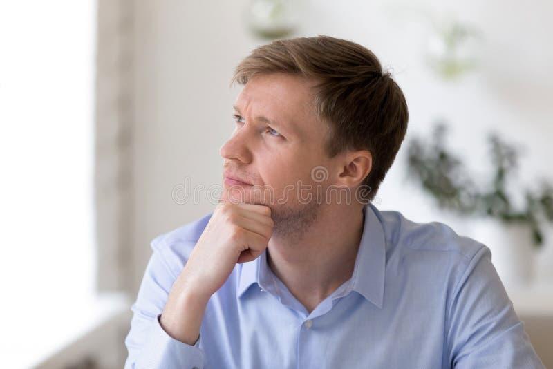 Durchdachter Geschäftsmann, der am Arbeitsplatz weg schaut sitzt stockfoto