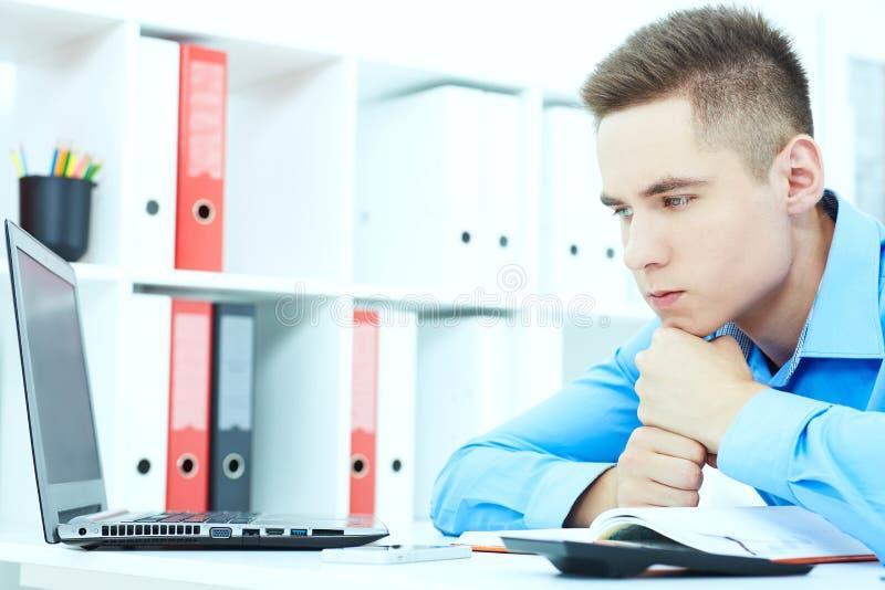 Durchdachter Geschäftsmann steht seinen Kopf auf seinen Fäusten und das Betrachten in den Abstand beim Sitzen seinem Arbeitsplatz lizenzfreie stockbilder