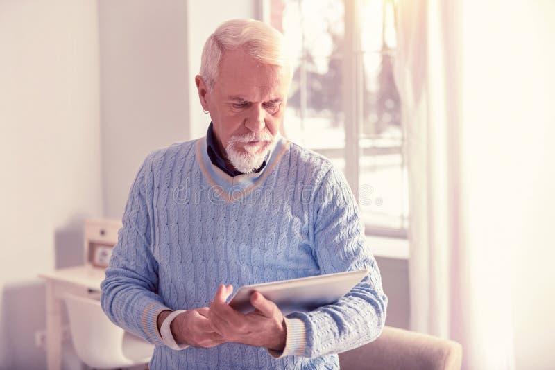 Durchdachter grau-haariger Mann, der moderne Tablette beschäftigt lizenzfreie stockfotografie