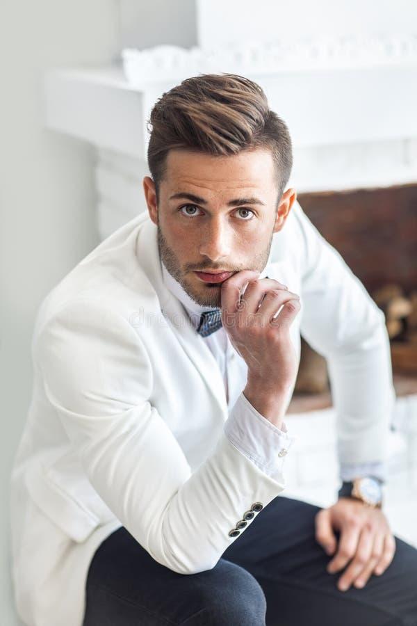 Durchdachter gutaussehender Mann, der sein Kinn berührt lizenzfreie stockfotografie