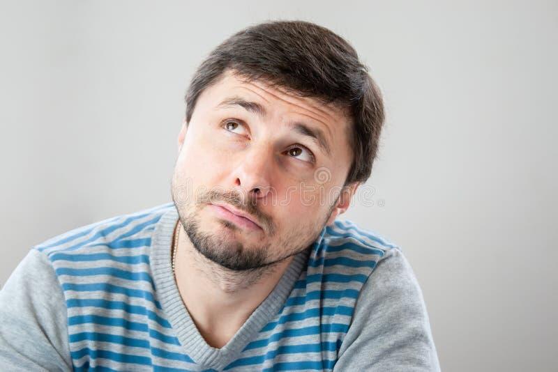 Durchdachter hübscher bärtiger Mann in einer gestreiften Strickjacke, die oben schaut lizenzfreies stockbild