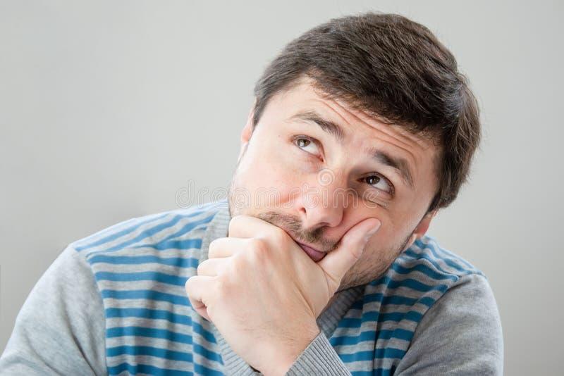 Durchdachter hübscher bärtiger Mann mit dem braunen Haar und den Augen in einer gestreiften Strickjacke, die seinen Kopf an seine lizenzfreies stockbild