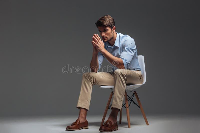 Durchdachter hübscher junger Mann, der auf Stuhl sitzt und weg schaut stockfotos
