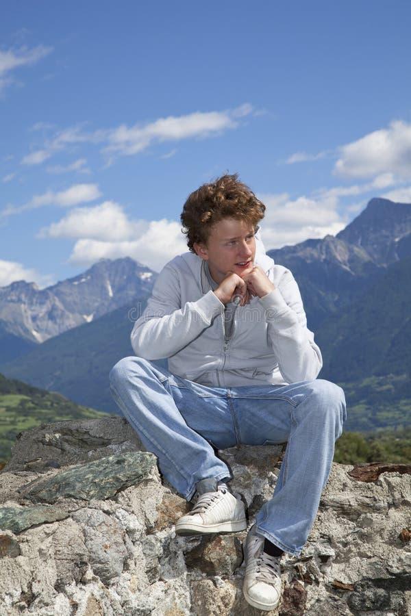 Durchdachter Jugendlicher, der auf einer Wand sitzt stockfotos