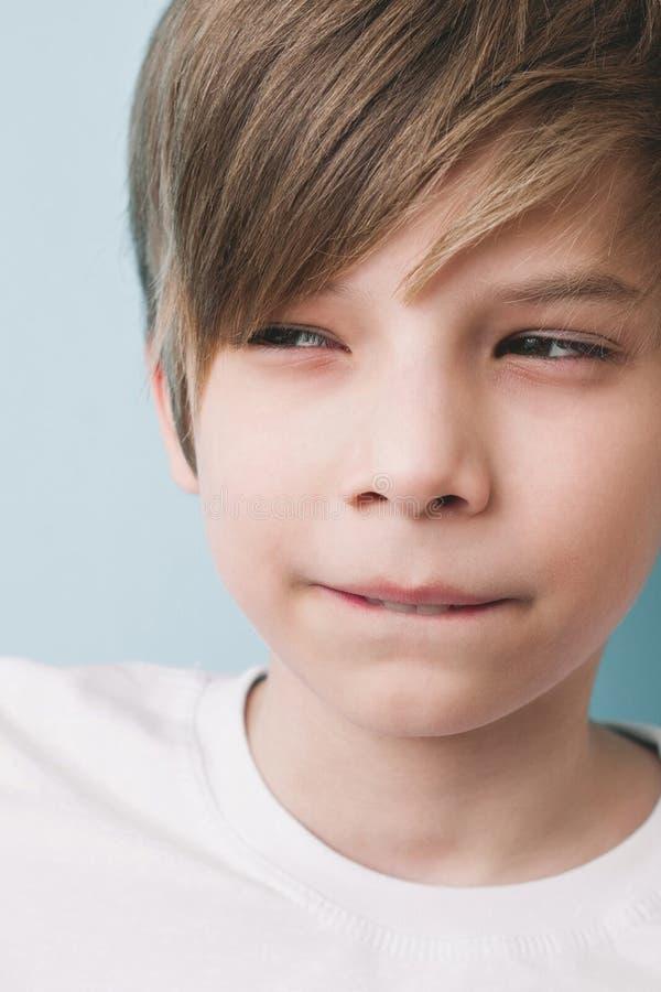 Durchdachter Junge mit bitterem Streich gebissen seiner unteren Lippe mit seinen Zähnen und verengt seinen Augen stockfotos