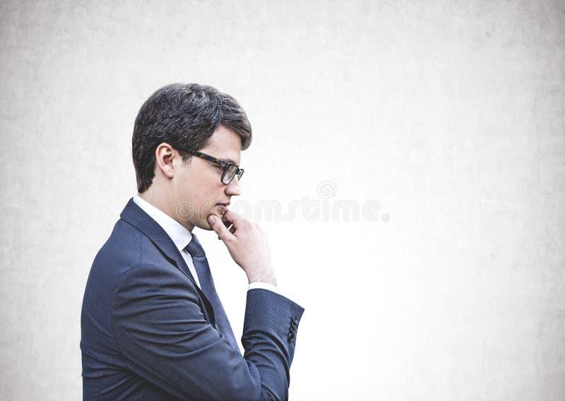 Durchdachter junger Geschäftsmann in den Gläsern, Schein oben lizenzfreie stockbilder