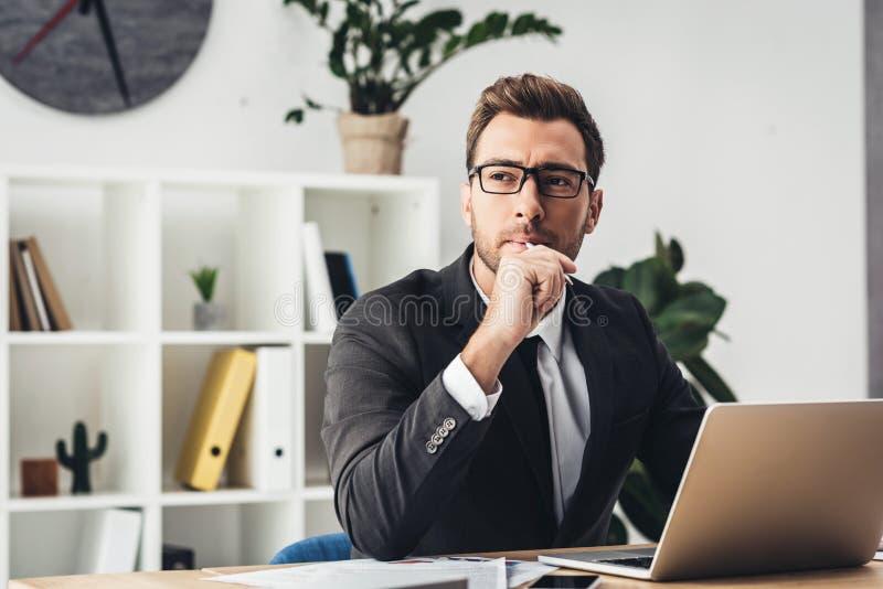 durchdachter junger Geschäftsmann an der Arbeitsplatzfunktion stockfotografie
