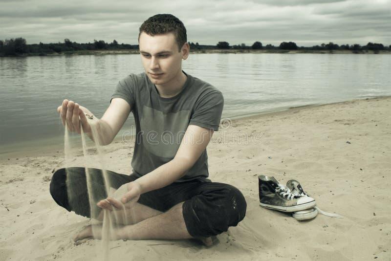 Durchdachter junger Mann, der auf dem Strand sitzt stockfotos