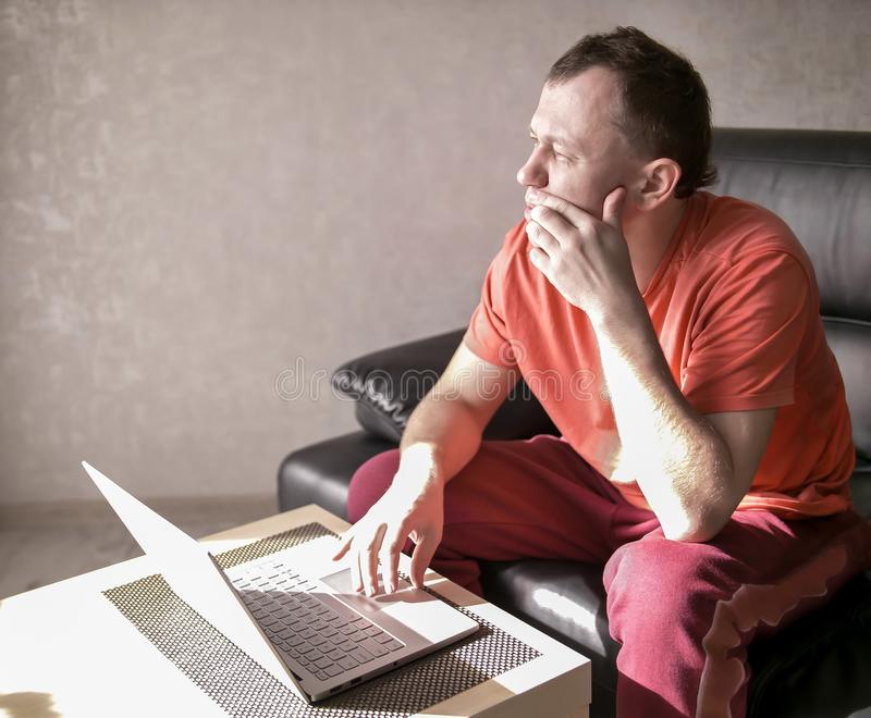 Durchdachter junger Mann, der nahe dem Laptop in ihrem Wohnzimmer, Copyspace sitzt lizenzfreie stockbilder