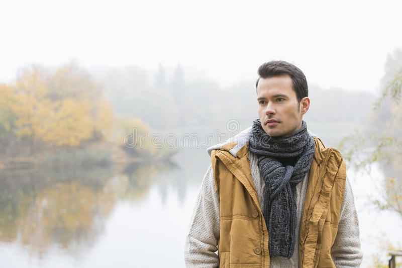 Durchdachter junger Mann in der warmen Kleidung, die gegen See steht stockbild