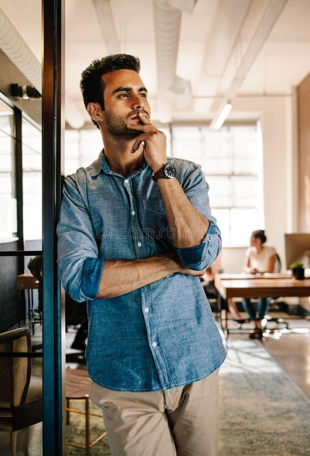 Durchdachter junger Mann im Startbüro stockbilder